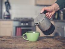 Кофе человека лить в кухне Стоковая Фотография RF