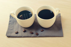 2 кофе эспрессо в малых белых чашках на серой салфетке Стоковая Фотография