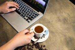 Кофе эспрессо в чашке горячего кофе и кофейных зерен, рук женщины работает, используя компьютер, пальцы девушки печатая на стоковые фото