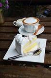Кофе Latte горячие и торт кокоса на таблице Стоковое Фото