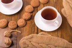 Кофе, mittens и печенье овса на древесине Стоковые Фотографии RF