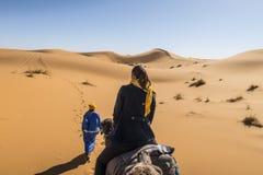 Кочевник Berber и девушка на верблюде в пустыне Сахары стоковая фотография