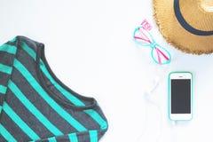 Коллаж одежд и аксессуаров плоского положения женственный с футболкой, шляпой с мобильным телефоном и наушником на белом backg Стоковая Фотография RF