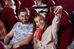 Кола подруги выпивая, принимая автопортрет с парнем в кино Стоковое Фото