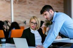 Коллегаы беседуя, сидящ совместно на таблице офиса, ся Стоковое Изображение RF