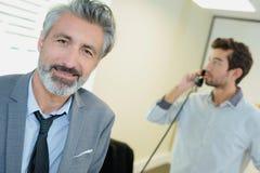 Коллега бизнесмена портрета на телефоне в предпосылке Стоковое фото RF