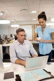 Коллега коммерсантки готовя мужской работая в офисе Стоковое фото RF