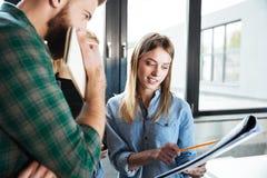 Коллеги в офисе говоря друг с другом держащ папку Стоковая Фотография