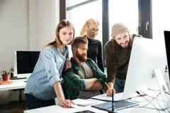 Коллеги в офисе говоря друг с другом используя компьютер Стоковые Изображения