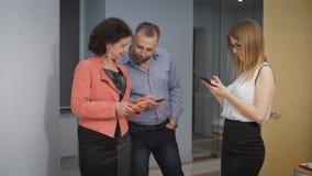 Коллеги в instagramm прихожей наблюдая Они смеются над, и обсуждаются фото и видео захваченные на телефоне сток-видео