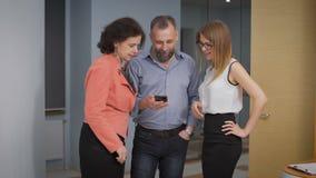 Коллеги в instagramm прихожей наблюдая Они смеются над, и обсуждаются фото и видео захваченные на телефоне видеоматериал