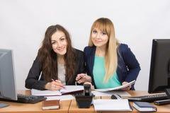 2 коллеги девушек совместно смотря документы офиса и посмотренные в рамку Стоковые Фотографии RF