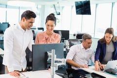 Коллеги дела взаимодействуя друг с другом на столе в офисе Стоковые Фото