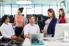 Коллеги дела взаимодействуя друг с другом на столе в офисе Стоковая Фотография RF