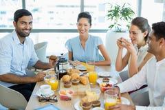 Коллеги дела взаимодействуя друг с другом пока имеющ завтрак Стоковое Изображение