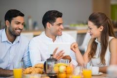 Коллеги дела взаимодействуя друг с другом пока имеющ завтрак Стоковое Фото