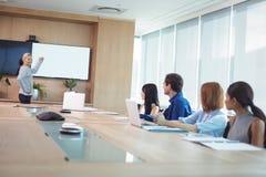 Коллеги дела на столе переговоров во время встречи Стоковое Изображение