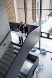 Коллеги дела обсуждая на светокопии пока стоящ на лестнице Стоковая Фотография