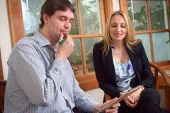 2 коллеги дела обсуждая документ проекта в офисе Стоковые Фотографии RF