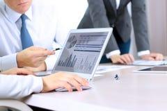 Коллеги дела работая и анализируя финансовые диаграммы/диаграммы на цифровой компьтер-книжке Стоковое Фото