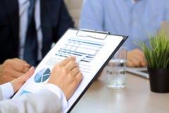 Коллеги дела работая и анализируя финансовые диаграммы на диаграммы Стоковая Фотография RF