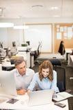 Коллеги дела работая на компьтер-книжке в офисе Стоковое Изображение RF