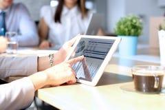 Коллеги дела работая совместно и анализируя финансовые диаграммы на цифровой таблетке Стоковая Фотография