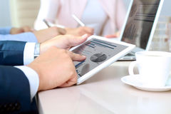 Коллеги дела работая совместно и анализируя финансовые диаграммы на цифровой таблетке Стоковые Изображения RF