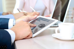 Коллеги дела работая совместно и анализируя финансовые диаграммы на цифровой таблетке Стоковое Изображение