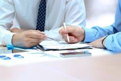 Коллеги дела работая совместно и анализируя финансовые диаграммы на диаграммы Стоковые Фотографии RF