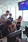 Коллеги дела работая совместно пока использующ технологии Стоковая Фотография
