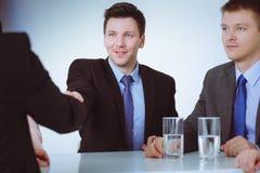 Коллеги дела сидя на таблице во время встречи с 2 мужскими тряся руками Стоковые Фотографии RF