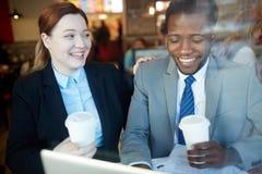 Коллеги дела смеясь над в кофейне после работы Стоковые Изображения