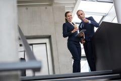 Коллеги дела стоя на лестнице и говоря друг к другу Стоковое Фото