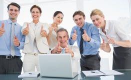 Коллеги дела с компьтер-книжкой показывать большие пальцы руки вверх на столе Стоковые Изображения RF