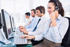 Коллеги дела с шлемофонами используя компьютеры Стоковое Фото