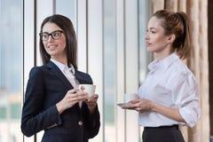 2 коллеги имея перерыв на чашку кофе совместно Стоковое Изображение