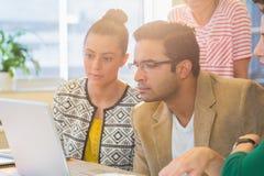 Коллеги используя компьтер-книжку в офисе Стоковое Фото