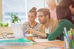 Коллеги используя компьтер-книжку в офисе Стоковое фото RF