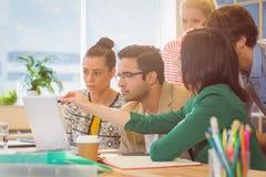 Коллеги используя компьтер-книжку в офисе Стоковая Фотография RF