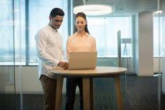 Коллеги используя компьтер-книжку в современном офисе Стоковые Фото