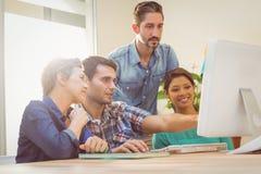 Коллеги используя компьтер-книжку на офисе Стоковое Изображение