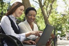 2 коллеги используя компьтер-книжку на скамейке в парке Стоковое Изображение RF