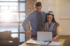 Коллеги используя компьтер-книжку на столе в офисе Стоковое фото RF
