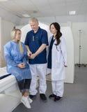 Коллеги и пациент с таблеткой цифров перед разверткой MRI Стоковые Изображения