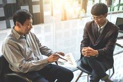 Коллеги команды 2 дела обсуждая диаграмму нового плана финансовую Стоковые Изображения RF