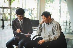 Коллеги команды 2 дела обсуждая диаграмму нового плана финансовую Стоковые Фотографии RF