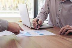Коллеги команды 2 дела обсуждая диаграмму нового плана финансовую Стоковая Фотография RF
