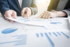 Коллеги команды 2 дела обсуждая финансовые данные по диаграммы дальше Стоковая Фотография