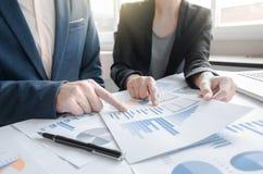 Коллеги команды 2 дела обсуждая финансовые данные по диаграммы дальше стоковые изображения